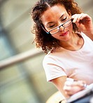 Pretty African American business woman making a note, looking through her specs