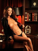 Beautiful sexy young woman sitting topless on a table