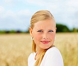 Closeup of a confident blond girl smiling at a field