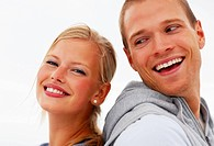 Back to back _ Happy young couple smiling against a white background
