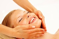 Closeup of a happy young female pampering herself with a facial by a masseuse