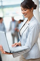 Happy young business woman using laptop with colleagues in the background