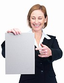 Portrait of charming mature businesswoman pointing and looking at a blank billboard isolated over white background