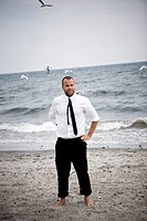 A business man standing on a beach, Skane, Sweden.