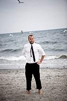 A business man standing on a beach, Skane, Sweden.