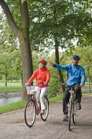 A couple cykling in a park, Sweden.