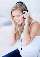 Cute young blond female listening to music over headphones