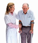 Portrait of a beautiful nurse helping a senior man on crutches against white