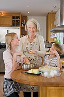 Grandchildren baking a cake with their grandmother, Sweden.