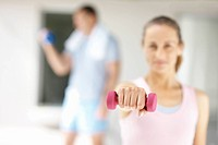 Blur image of a woman working out with a dumbbell at the gym and man at the back