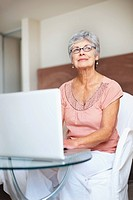Thoughtful retired woman using a laptop while at home
