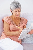 Portrait of an elderly woman solving a crossword puzzle in newspaper