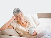 Portrait of a relaxed senior woman drinking coffee while smiling on couch