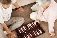 Top view of a retired old couple playing a game of backgammon on the floor