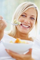 Closeup portrait of a beautiful middle aged woman eating a healthy bowl of cut fruits