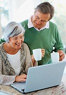 Happy retired couple drinking coffee and browsing the internet together on a laptop
