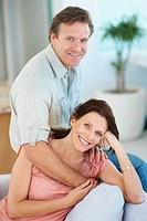 Cute middle aged couple smiling while at home