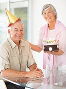 Senior woman celebrating husband´s birthday with a cake and lit candles