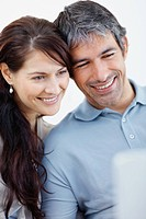 Closeup of a happy casual couple looking at laptop _ White background