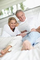 Happy mature couple sitting in bed and reading the daily newspaper together