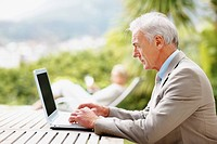 Profile of a senior business man working on a laptop outdoors with wife at the background