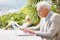 Senior woman relaxing on a recliner at the lawn with husband using a laptop