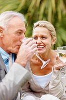 A cheerful couple enjoying while drinking wine outdoors