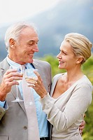 A beautiful cheerful couple toasting wine glasses outdoors