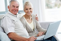 Portrait of a happy elderly couple using a laptop the browse the internet at home