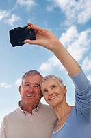 Self portrait photography _ Happy senior couple smiling below cloudy sky