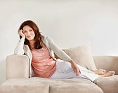 Pretty relaxed middle aged woman relaxing on a couch at home