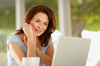 Smiling middle aged brunette looking at laptop
