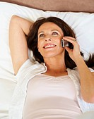 Pretty relaxed middle aged woman using cellphone
