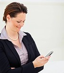 Pretty middle aged woman reading an SMS while at work