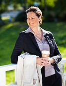 Pretty middle aged business woman by railing at a park holding disposable coffee