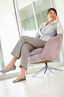 Young business woman waiting for someone while sitting on a chair
