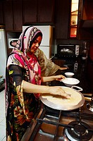 Oman, Sultanat, Middle East, Muscat, women fixing bread in the kitchen for lunch and having lunch, Hamza-Hayyat family.