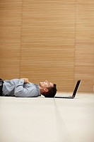 Happy young man lying on floor with a laptop near his head