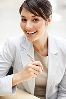 Portrait of a cheerful Business woman sitting on her desk holding a pen