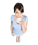 Top view of a pretty young female in blue drinking a glass of milk _ White background