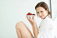 Cute young caucasian female sitting with a plate of strawberries by the window