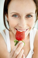 Closeup portrait of a cute female holding a bitten strawberry