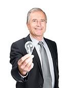 Portrait of a handsome mature business man holding a light bulb