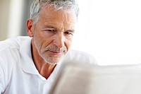 Closeup portrait of a senior man reading a newspaper _ Copyspace