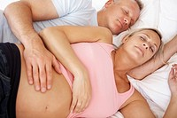 Closeup of mature pregnant couple sleeping together on the bed