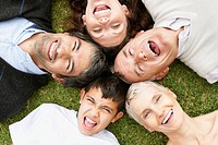 Closeup of a happy multi generational family lying on grass