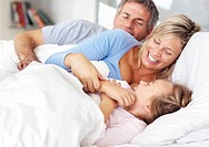 Happy young family enjoying themselves after wake up on the bed at home