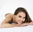 beuatiful caucasian woman lying on a white bed