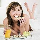 woman lying on a white bed holding orange juice