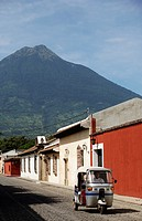 A tuktuk or moto taxi in a street in Antigua in Guatemala with the Volcan de Agua in the background